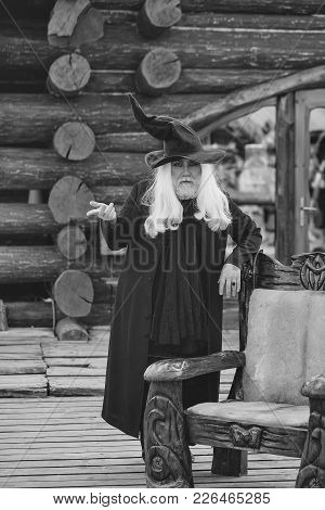 Old Man Wizard With Long Grey Hair Beard In Black Costume And Hat For Halloween Standing Near Wooden