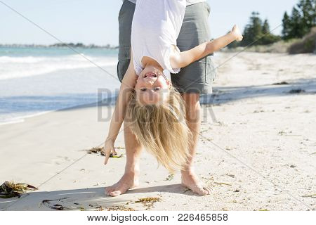 Father Holding Sweet Young And Lovely Blond Small Daughter By Her Feet Playing Having Fun On The Bea