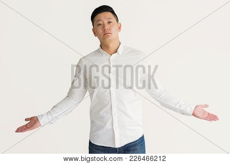 Indifferent Asian Businessman Does Not Know Answer And Shrugging Shoulders. Displeased Handsome Youn