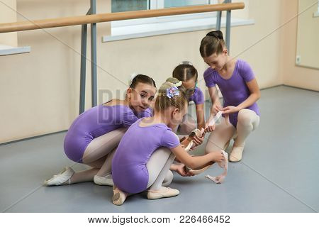 Four Young Ballerinas In Ballet Class. Group Of Young Beautiful Ballet Dancers Having Communication