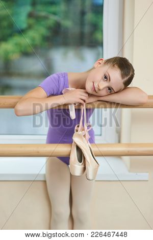 Cute Little Ballerina With Ballet Shoes. Happy Little Female Ballet Dancer With Ballet Slippers On B