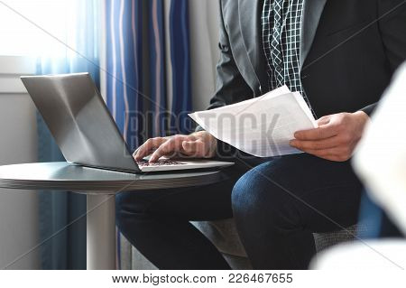 Businessman In Hotel Room Reading Business Report Paper. Man Working With Laptop. Lawyer Holding Leg