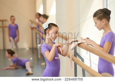 Young Beautiful Ballerinas Close Up. Two Lovely Girl With Ballet Shoes In Ballet Dance Studio. Frien