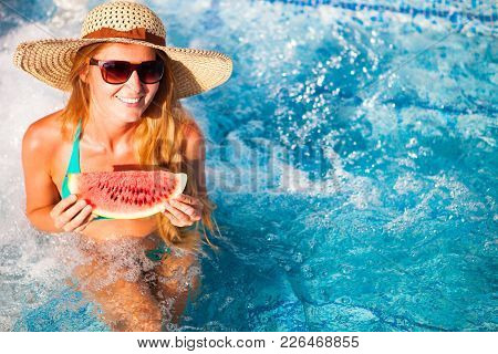 A Girl Holds Half A Red Watermelon  Over A Blue Pool, Relaxing On Spa In A Tropical Hotel, Eating He