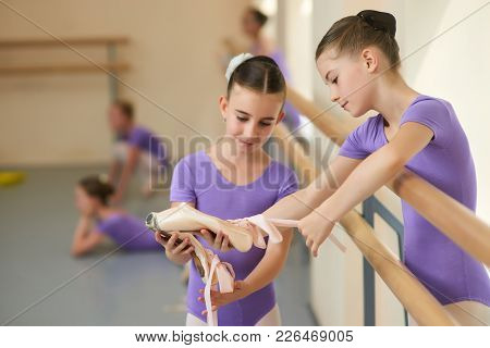 Teen Ballerina Showing Her Slippers To Friend. Little Ballerinas Having A Rest. Beautiful Ballet Dan