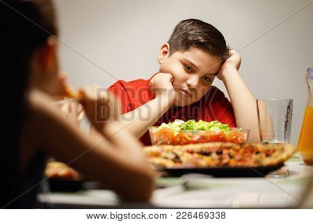 Hispanic family with mom, fat son and daughter having dinner at home, eating salad and pizza. Latino people with mother, overweight boy and girl during meal. poster