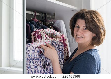 Woman Hanging A Blouse In A Closet On A Hanger