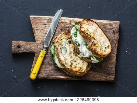 Spinach Mozzarella Grilled Ciabatta Bread Sandwich On Rustic Cutting Board On Dark Background