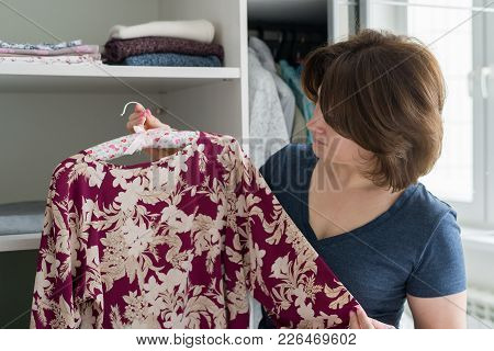 A Woman Chooses A Blouse In The Closet In The Apartment