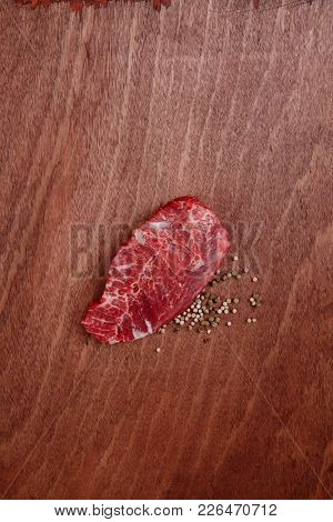 fresh raw beef meat steak with white and green peppercorn spice on walnut table empty space for text