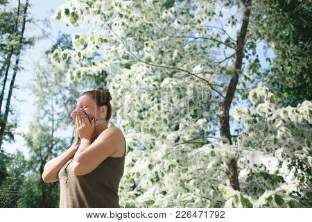 Young Woman Suffering Spring Pollen Allergy. Poplar Bloom Season.