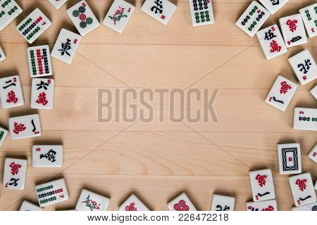 White-green Tiles For Mahjong On A Background Of Light Brown Wood. Empty Space In The Center