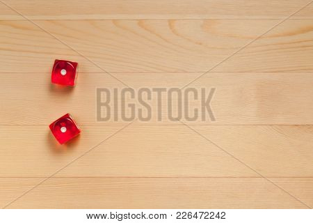 Red Dice On A Light Brown Wooden Background. Discarded 2 (1 And 1)