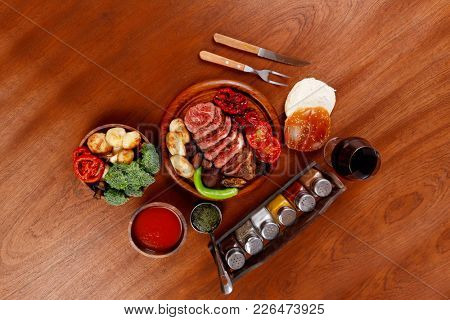 fresh roast bbq beef meat rib eye steak on wooden plate served with tomato juice in wooden cup, boiled broccoli, baked tomatoes and potatoes, white bun, and red wine glass on light walnut wooden table