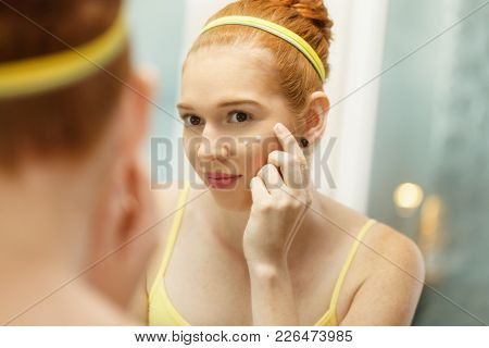 Young Woman Applies Anti-aging Cream Looking At Mirror