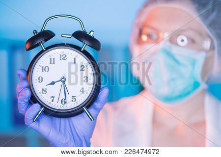 Female Surgeon Medical Specialist With Clock Emphasizing The Importance Of Regular Health Care Medic