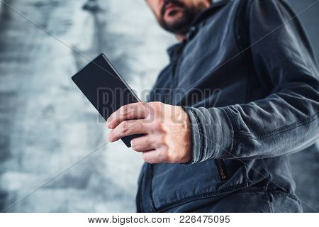 Low Angle View Of Casual Adult Man Reading Private Sms Text Message On His Personal Mobile Phone