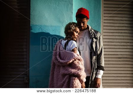 Pensive  Woman With Trendy Hairtyle And Her Dark Skinned Stylish Boyfriend In Red Hat, Stand Close T