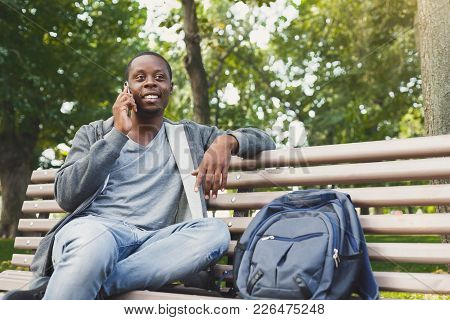 Smiling African-american Student Sitting And Talking On The Phone On The Bench Outdoors, In Universi