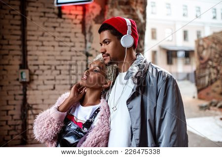 Attractive  Woman And Her Dark Skinned Stylish Friend Who Listens Music With Headphones, Walk Togeth