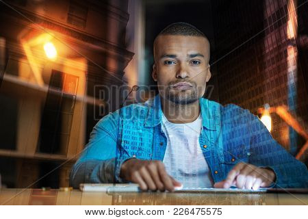 Looking Serious. Calm Young Serious Man Thoughtfully Looking Into The Distance While Sitting At The