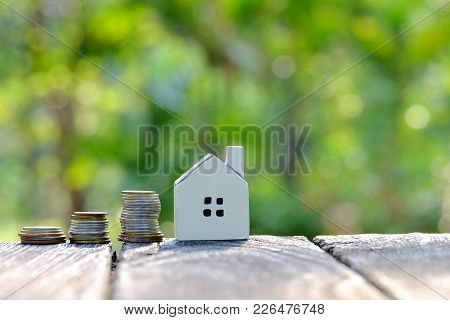 A House Model With A Row Of Coins On The Old Wooden Table With Sunlight And Green Bokeh At The Park