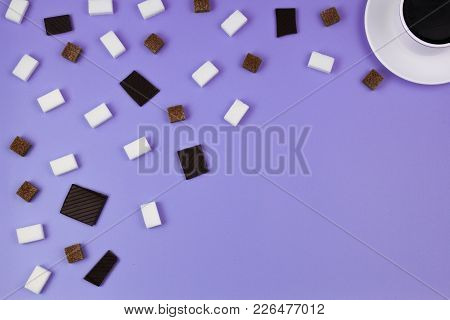 White Cup Of Coffee, Brown And White Sugar Cubes And Chocolate Prieces On Violet Background. Top Vie