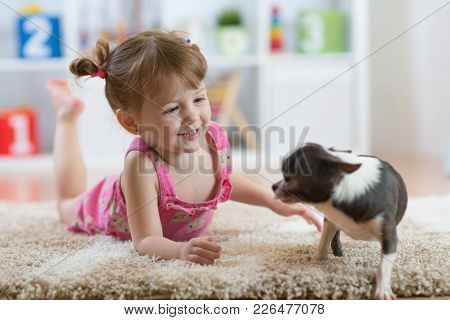 Child Playing With The Dog Lying On Floor At Home