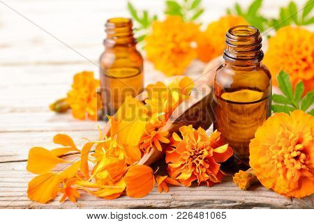 Tagetes Essential Oil And Flowers On The Wooden Table