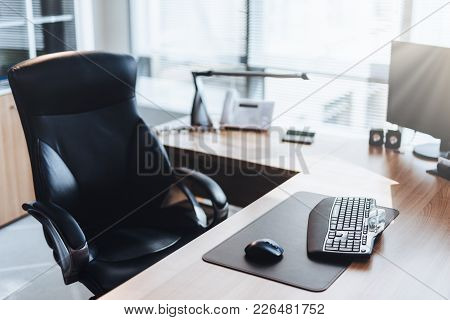 Workplace Of Businessman: Computer, Wooden Table And Chair In Cabinet. Office Style. Modern Equipmen