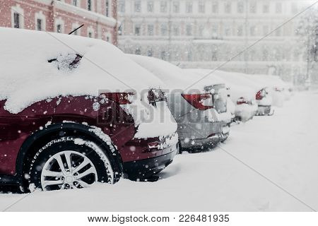 Parked Cars Stuck In Snow After Heavy Snowstorm Stand At Parking Lot. January Snowfall In City. Tran