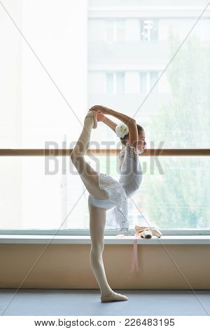 Ballerina Doing Exercise Before Performance. Young Teenager Ballerina In Elegant White Dress Practic
