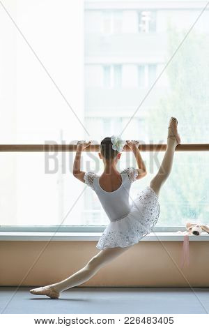 Ballerina Stretching Leg, Back View. Young Ballet Girl In Beautiful Dress Training Stretch Of Her Le