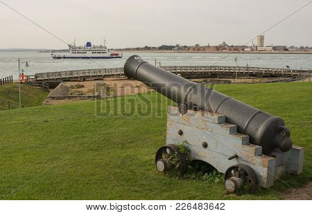 Old Naval Cannon At Entrance To Portsmouth Harbour In Hampshire, England. With Isle Of Wight Ferry B