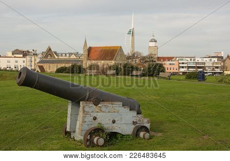 Old Naval Cannon At Entrance To Portsmouth Harbour In Hampshire, England. With Gunwharf Quays And Sp