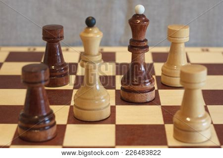 Closeup Image Of A Board Game Chess On A Gray Background White And Black Figures.