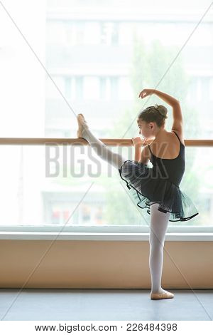 Young Ballet Performer Training At Class. Cute Little Ballerina In Black Leotard Doing Exercise At B