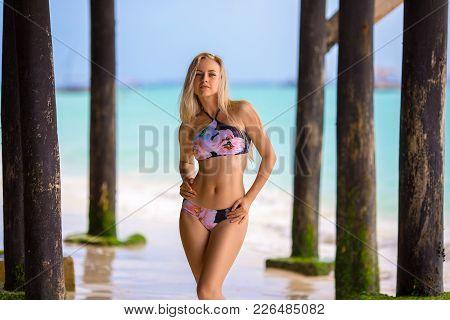 Beautiful Blonde Woman In The Bikini Posing On The Lonely Beach Near The Old Wooden Port. Zanzibar.