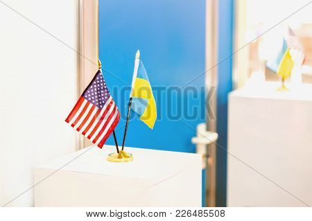 Ukrainian And Usa Flags Stand Together. Closed Door On The Background. Government Negotiations. Part