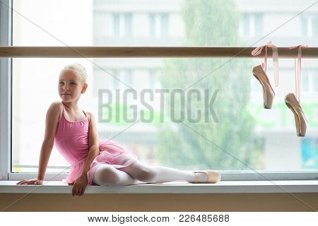 Lovely little ballerina posing at window-sill. Beautiful ballet dancer in pink leotard and ballet slippers. Pair of ballet shoes hanging on training barre. poster