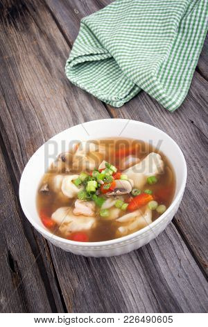 Dumpling Soup With Green Onion On Rustic Wood Table