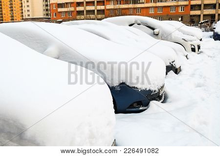 Parked Cars In The Yard Covered With Snow