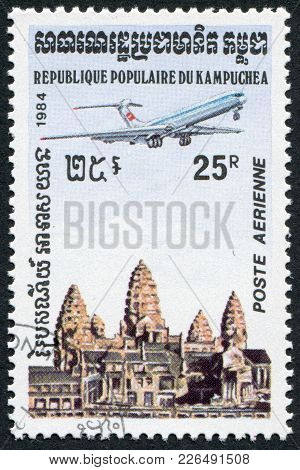 Kampuchea-circa 1984: A Stamp Printed In The Cambodia, Shows The Plane On The Background Of Angkor W