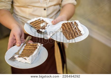 Waiter Holding Plate With Tasty Wedding Cake, Close Up View