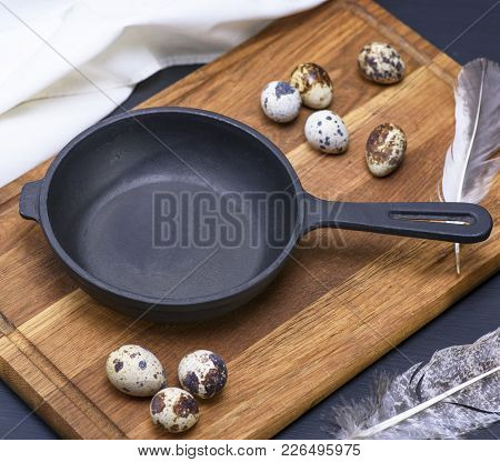 A Round Empty Black Cast-iron Frying Pan And Quail Eggs In A Rump On A Brown Wooden Board