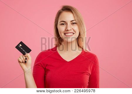 Cheerful Delightful Blonde Woman Holds Plastic Card, Happy To Go Shopping And Recieve Lump Sum Of Mo