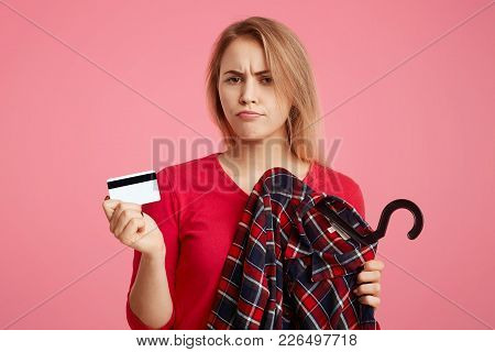 Photo Of Lovely Woman With Discontent Expression Goes Shopping In Fashionable Boutique, Chooses Outf