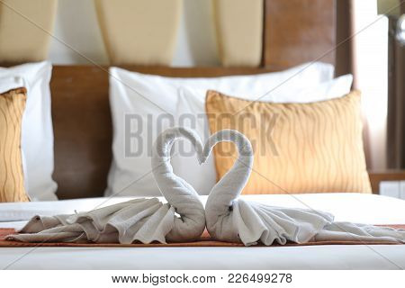 Two Swans Made Of Towels Forming Heart Shape On Bed In Honeymoon Suite Room Hotel Decorated For Wedd