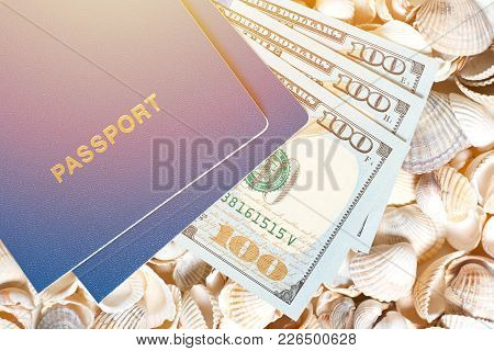 Passport And Dollars On Shells Background Demonstrate Expensive Travelling, Tourism And Tours In Oth