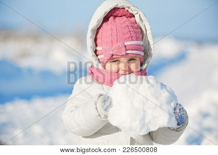 Lovely Pretty Little Girl Dressed In Warm Winter Clothes, Holds Snowball Relaxes Outdoor During Fros